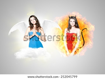 Beautiful young brunette woman as devil and angel - concept portrait - stock photo