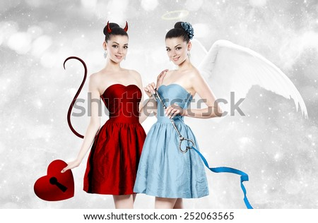 Beautiful young brunette woman as devil and angel - concept portrait