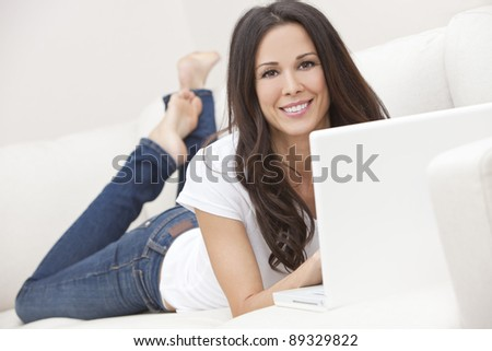 Beautiful young brunette woman at home laying on sofa or settee using her laptop computer and smiling - stock photo
