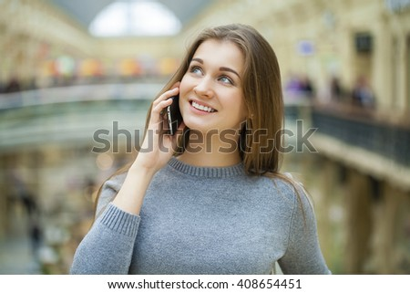 Beautiful young brunette woman calling by phone in the shop - stock photo