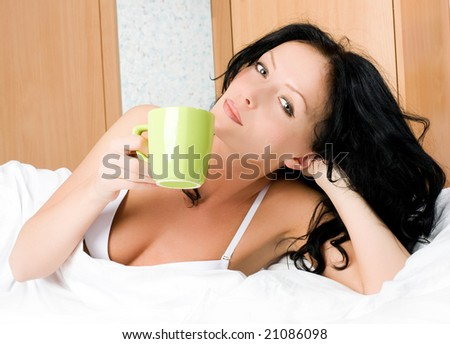 beautiful young brunette woman drinking coffee in bed in the morning - stock photo