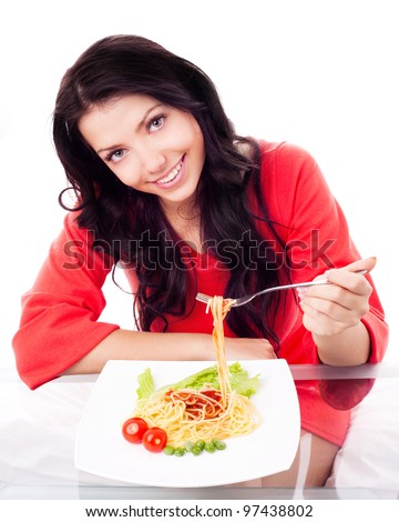 beautiful young brunette woman  eating spaghetti with vegetables and ketchup at home