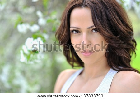 Beautiful young brunette woman face outdoor - stock photo