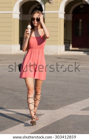 Beautiful young brunette woman having ice cream refreshment in summer sunshine.