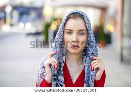 Beautiful young brunette woman in a blue scarf on summer street city - stock photo