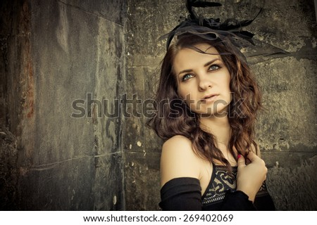 Beautiful young brunette woman in a vintage style in evening black dress on the street in the old castle - stock photo