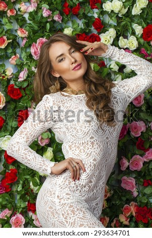 Beautiful young brunette woman in classy white dress on flower wall background