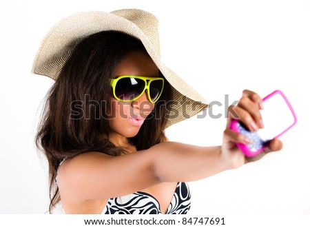 Beautiful young brunette woman in cowboy hat and sunglasses taking a photograph with a mobile cell phone - isolated on white - stock photo