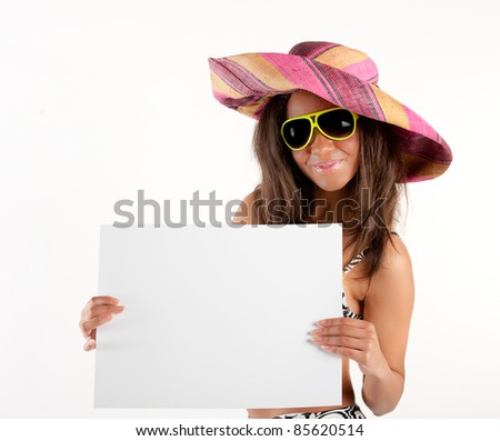 Beautiful young brunette woman in cowboy hat and yellow sunglasses displaying billboard for copy space - stock photo