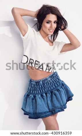 beautiful young brunette woman in nice jeans skirt, white top, sneakers shoes posing in a studio. Fashion spring summer photo - stock photo
