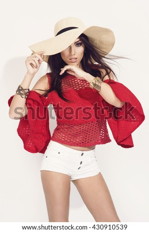 beautiful young brunette woman in nice red blouse, summer hat, white shorts, high heels shoes posing in a studio. Fashion spring summer photo