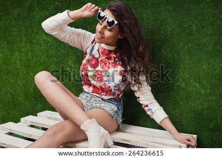 beautiful young brunette woman in nice spring dress, posing in studio on grass. Fashion photo, white shoes, sunglasses - stock photo