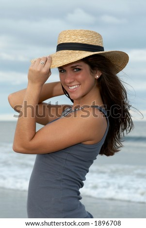 Beautiful Young Brunette Woman in Straw Hat at the Beach