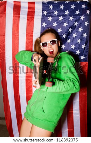 beautiful young brunette woman in style cloth and sunglasses sucking lollipop with national usa flag in background, outdoors - stock photo