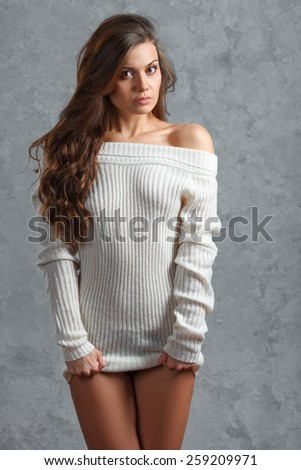 Beautiful young brunette woman in sweater over gray background - stock photo