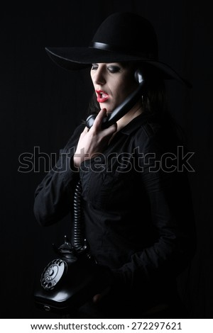 beautiful young brunette woman lady posing in a studio on a black background with old style hat  holding a telephone