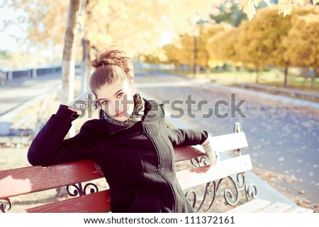 Beautiful young brunette woman on a bench in autumn - stock photo