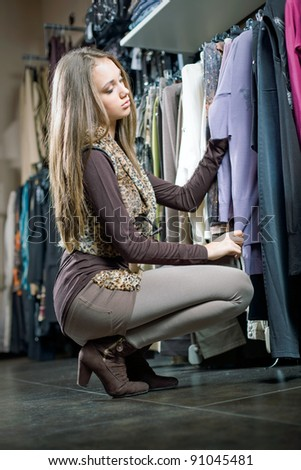 Beautiful young brunette woman on a shopping spree showing off new clothes. - stock photo