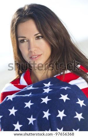 Beautiful young brunette woman or girl at the beach wrapped in stars and stripes american flag towel