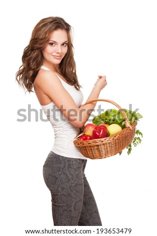 Beautiful young brunette woman posing with basket of fresh vegetables.