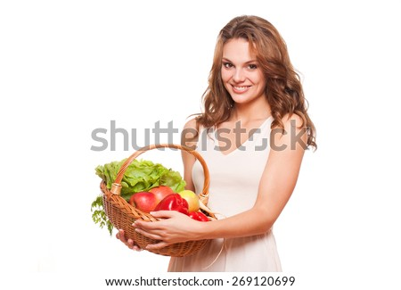 Beautiful young brunette woman posing with basket of fresh vegetables. - stock photo