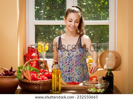 Beautiful young brunette woman preparing healthy food in the kitchen. - stock photo