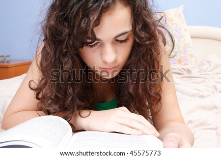 beautiful young brunette woman reading a book on the bed at home - stock photo