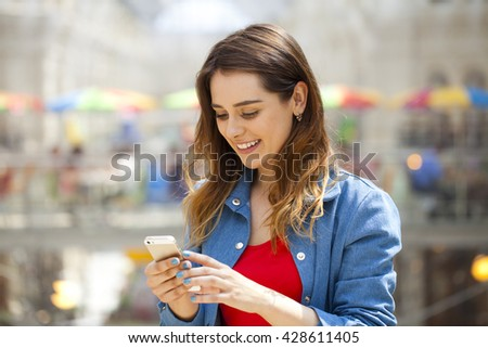 Beautiful young brunette woman reading a message on the phone