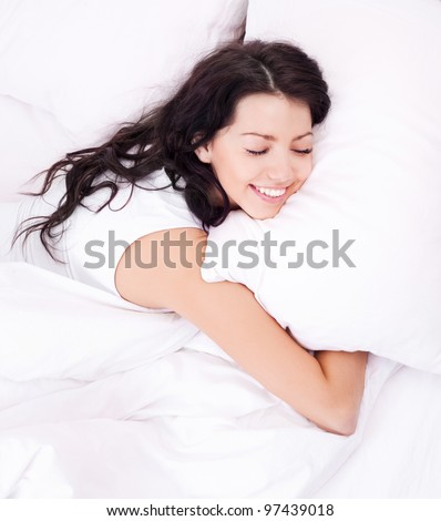 beautiful young brunette woman relaxing in bed at home - stock photo
