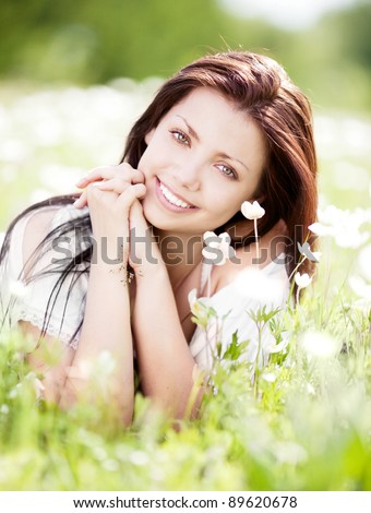 beautiful young brunette woman relaxing on the  meadow with white flowers  on a warm summer day - stock photo