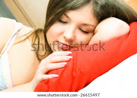 beautiful young brunette woman sleeping peacefully in her bed - stock photo