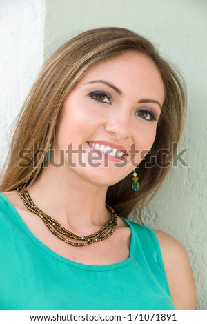 Beautiful young brunette woman smiling outdoors  - stock photo