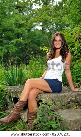 Beautiful young brunette woman standing in a white tank top and denim mini skirt (with cowboy boots) sitting on a concrete slab among green vegetation - smiling - stock photo