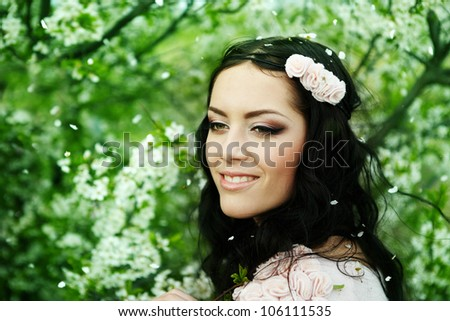 Beautiful young brunette woman standing near the apple tree - stock photo