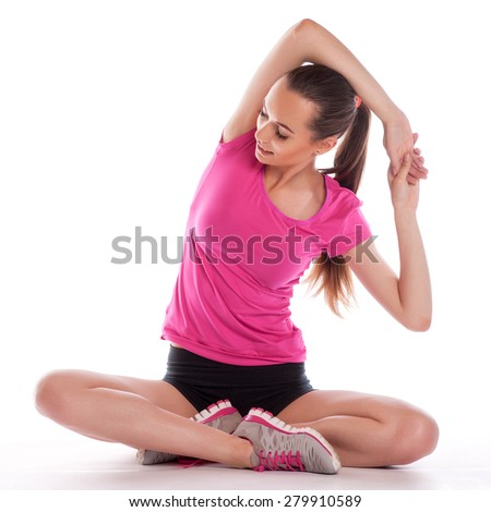 beautiful young brunette woman stretching the muscles of her arms and back - stock photo