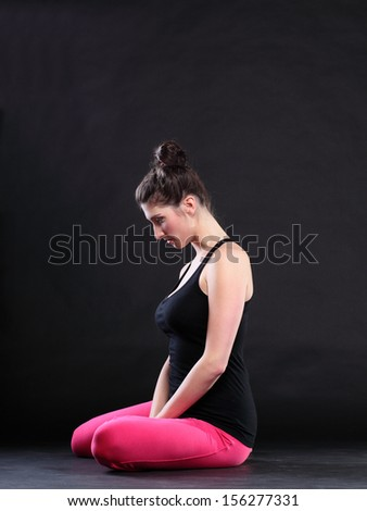 beautiful young brunette woman stretching the muscles of her arms and back, isolated against black background - stock photo