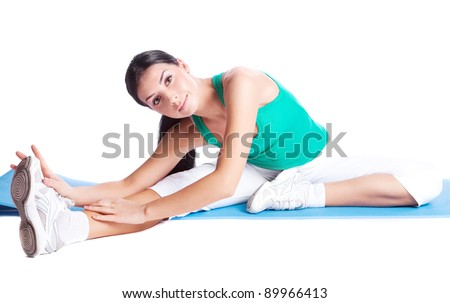 beautiful young brunette woman stretching the muscles of her legs, isolated against white background - stock photo