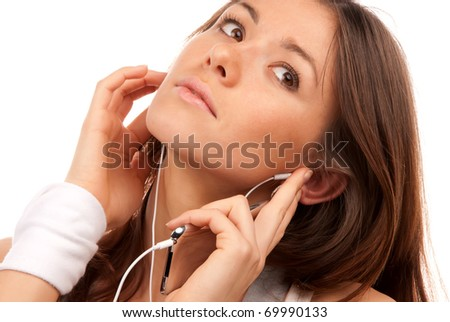 Beautiful young brunette woman talking on new cellphone mobile in earphones isolated on a white background - stock photo