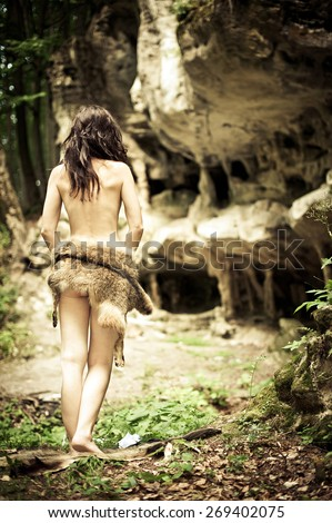 Beautiful young brunette woman wearing a wolf skin in the green forest near the ancient caves - stock photo