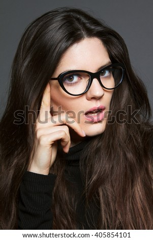 Beautiful young brunette woman wearing black clothes and nice strict black glasses.