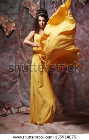 beautiful young brunette woman wearing yellow evening dress - stock photo