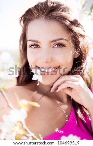 beautiful young brunette woman with a flower in her teeth standing near the apple tree on a warm summer day - stock photo