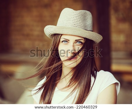 Beautiful young brunette woman with a hat - stock photo