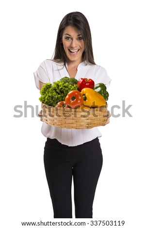Beautiful young brunette woman with a wicker basket full of vegetables and fruits