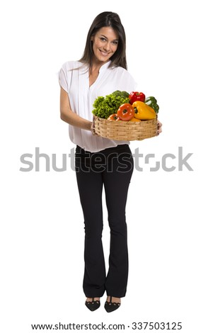 Beautiful young brunette woman with a wicker basket full of vegetables and fruits - stock photo