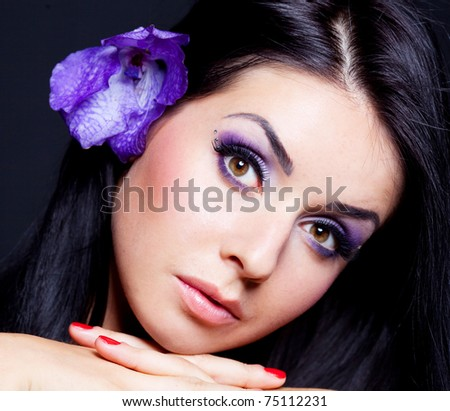 beautiful young brunette woman with  an orchid in her hair - stock photo