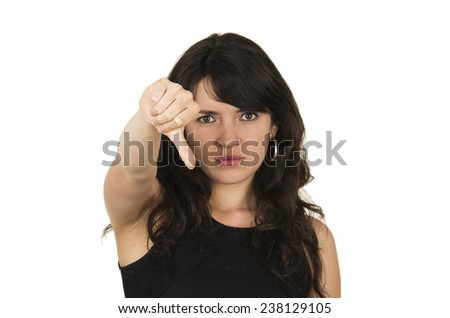 beautiful young brunette woman with black top holding thumb down concept of negative disappointment isolated on white