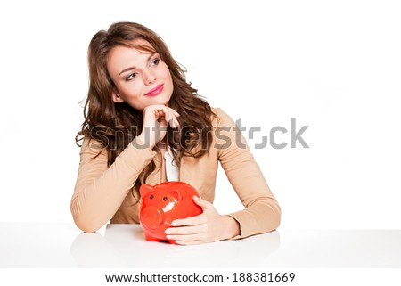 Beautiful young brunette woman with bright orange piggy bank.