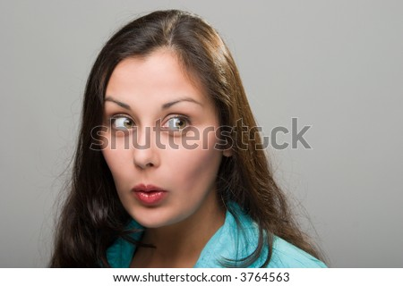 Beautiful young brunette woman with facial expression of surprise, excitement, embarassment, or amazement. - stock photo