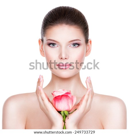 Beautiful young brunette woman with healthy skin and pink flowers near face - isolated on white. - stock photo